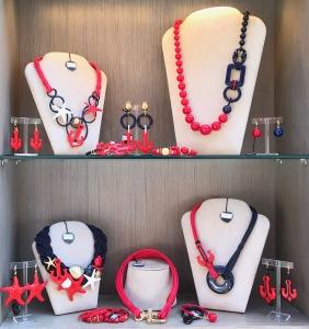 Una delle nostre vetrine in rosso e blu con luminosi flash bianco latte e brillanti dettagli gold: creazioni originali e divertenti per gli outfit di primavera.