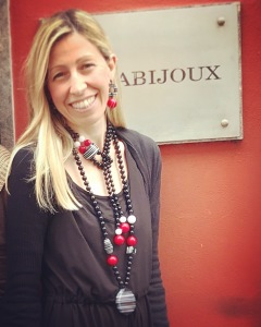 """Raffy indossa due collane della collezione """"Red Carpet"""": una più corta a frustino e una lunga con pendente centrale, entrambe realizzate con boulle ed elementi in plexiglas nella combinazione bianco, rosso e nero."""
