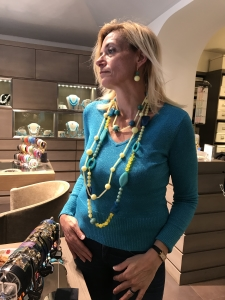 """Sabrina indossa un gruppo di collane della collezione """"Denim & Colours"""": una con boulle ed elementi fantasia, una con sfere e cilindretti, un girocollo con sfere e cilindretti. Orecchini con doppia boulle a gradazione. Tutti bijoux realizzati a mano in plexiglas nelle vivaci nuance del turchese, azzurro denim e giallo."""