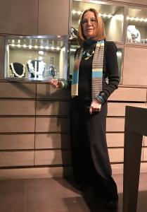 Cilla indossa una collana molto originale, realizzata con una mezzaluna in legno e tanti pendenti in turchese, legno e cialde ricoperte in preziosa foglia d'oro. Un pezzo unico, di grande effetto, eppure molto versatile.