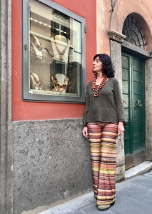 Sandra indossa una collana nei toni del corallo e mattone, realizzata con elementi in legno e madrepore naturali, centrale in legno con pendenti.