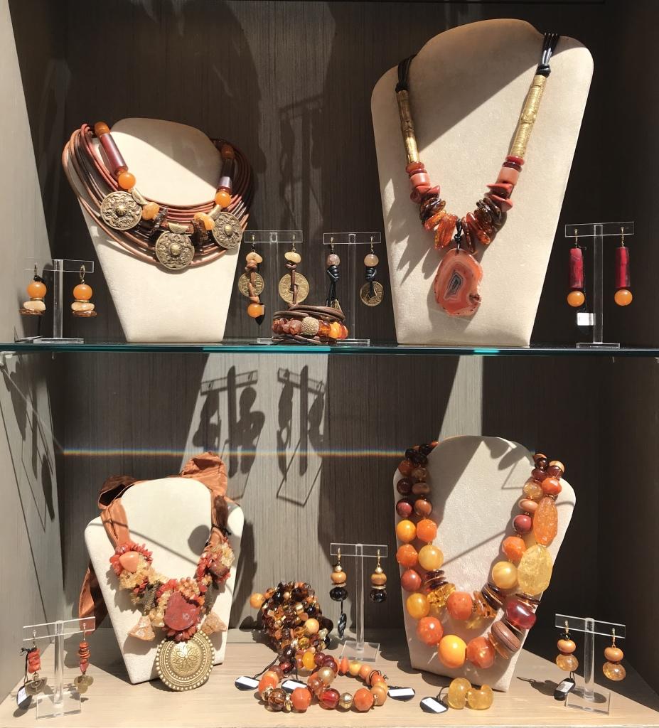Una delle nostre vetrine nelle calde nuance ambrate con creazioni uniche realizzate con preziose pietre dure, ambre naturali, corno vegetale ed elementi in bronzo.