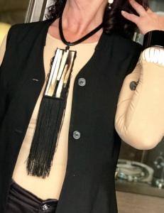 Sandra indossa una collana realizzata con filato in cotone cerato con grande piastra lavorata: tanti pezzi di osso inglobati nella resina e lunga frangia in tripolina di seta. Anche questa è un pezzo unico, di Cillabijoux