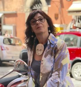 Sandra indossa una collana molto originale, realizzata con filato in cotone cerato azzurro jeans e grande mascherone centrale in plexiglas metallizzato argento, con effetto martellato.