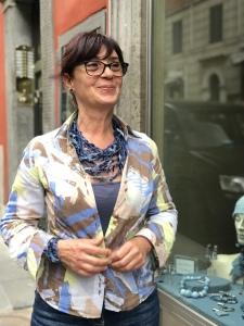 """Sandra indossa una originalissima collana realizzata interamente a mano con filato in cotone cerato e tantissimi fiocchettini di jeans. È un pezzo unico della collezione """"Jeans special Summer"""". Da abbinare il bracciale realizzato con la stessa lavorazione a fiocchetti."""