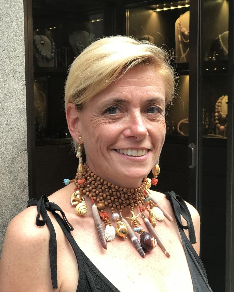 Bellissima la nostra Sabri con questo collier de chain realizzato interamente a mano con una maglia di sfere in legno e tanti pendenti a tema marino: conchiglie naturali, cassetti in corallo e turchese, elementi in plexiglas metallizzato.