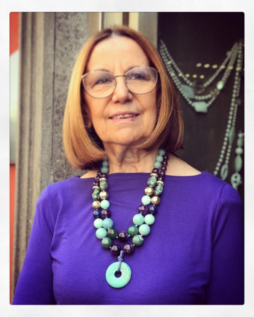Cilla indossa due collane realizzate con splendide pietre dure nei toni del turchese, viola e verde smeraldo. Sono pezzi unici di Cillabijoux