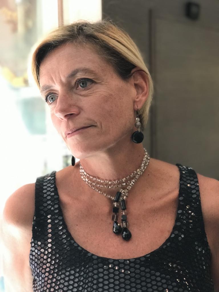 Sabrina indossa una collana in Cristallo beige con pendenti in Onice, da indossare in tanti modi diversi: qui la vedete girata tre volte per un effetto collier de chain. Orecchini in Cristallo e Onice in parure.