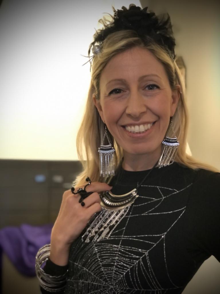 """Raffy  indossa una collana con tanti ciondoli nei toni dell'argento e nero, realizzata con tanti elementi metallici a bacchettina, come gli orecchini. Divertenti il cerchietto con fiori e piume e l'anello """"ragno"""" in Cristallo."""