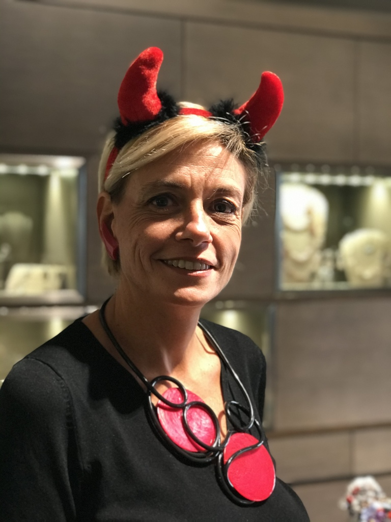 Sabrina  indossa una originalissima collana realizzata e modellata interamente a mano con rubber tube nero e due grandi dischi in kapiz di madreperla rossi. È un pezzo unico di Cillabijoux Orecchini a virgola rosso lacca.