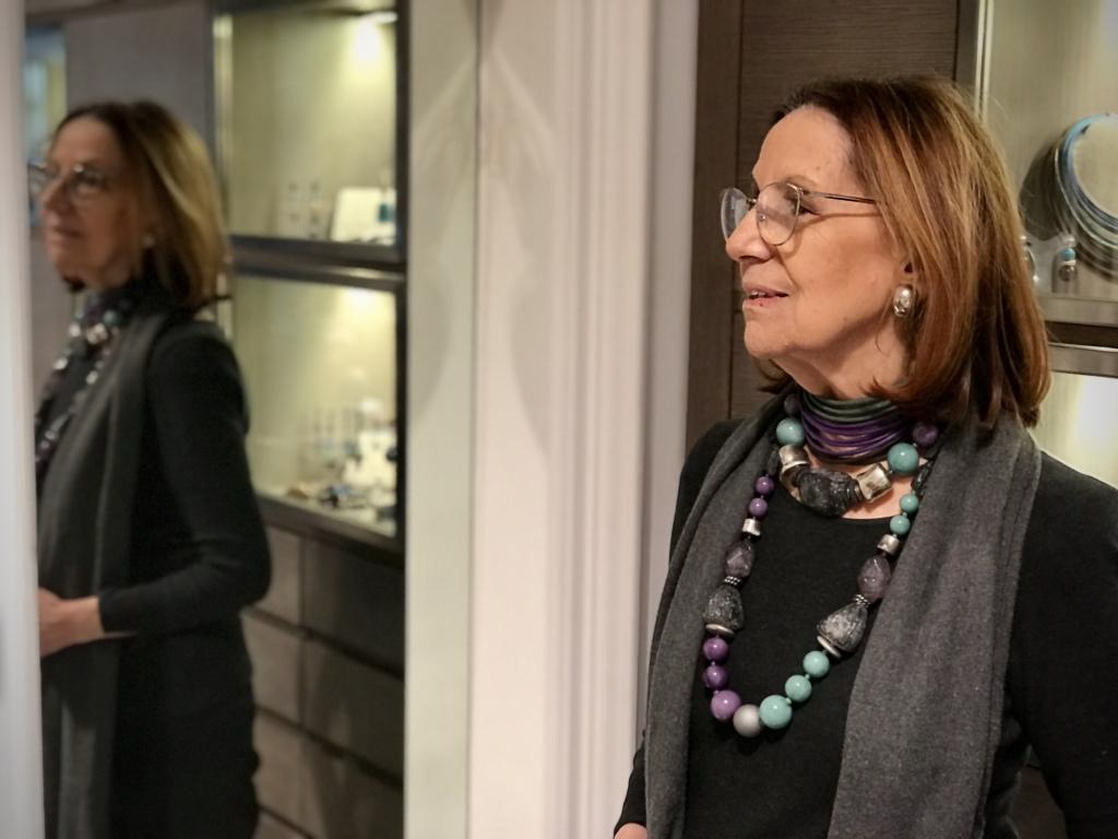 Cilla indossa due collane, un girocollo e una lunga, realizzate con boulle ed elementi in plexiglas, nei toni del grigio, viola e verde marino. Nelle stesse nuance anche il collier de chain a fascia.