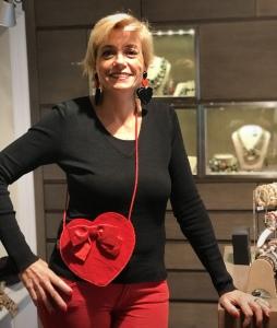 Sabrina indossa maxi orecchini in plexiglas con doppio cuore, uno nero e uno rosso e una deliziosa pochette a forma di cuore, rosso fuoco.  La pochette è un pezzo unico, interamente cucita a mano, con grande fiocco in velluto e cordino in seta.