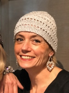Sabrina indossa indossa un cappellino calotta in lurex platino ed orecchini a forma di cuore con cristalli Swarovski