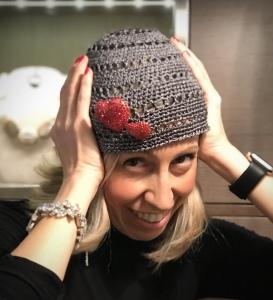 Raffy indossa un cappellino a calotta in lurex grigio argento con due spille a cuore ricoperte di strass Swarovski rosso vivo.