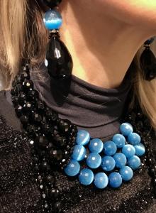 Dettaglio dei gioielli: Collier de chain a tre fili di Cristalli Jais nero e azzurri e collane lunghe, tutte realizzate interamente a mano con elementi in Onice, Cristalli in Jais nero e azzurri. Luminosità eccezionale ed un tocco di colore che renderà unico anche un look semplice total black. Preziosi ed eleganti questi gioielli regaleranno un'allure sofisticata e glamour al tuo look. Maxi orecchini in cristallo con grande goccia Jais nero.