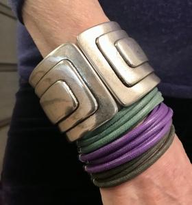 Cilla indossa due bellissimi bracciali: Uno a scatto, in plexiglas metallizzato argento, con motivi geometrici, essenziale e d'effetto. L'altro è un bracciale realizzato interamente a mano con fili di cotone cerato che formano fascia intorno al polso.