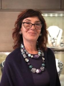 Sandra indossa due magnifiche collane in pietra dura, corno vegetale e plexiglas: un mix inedito ed accattivante che unisce versatilità ed originalità. Orecchini a bottone in plexiglas metallizzato argento.