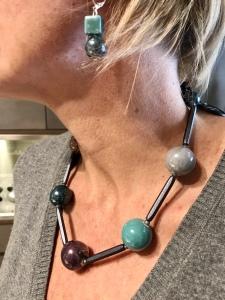 Dettaglio del girocollo e degli orecchini indossati da Sabrina. Da notare la luminosità delle boulle in ceramica, in raffinate nuance dal grigio al prugna, dal beige al verde marino.
