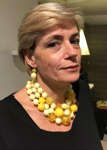 Sabrina indossa una collana a tre fili (indossabile anche più accollata a collier de chain) realizzata a mano con tante boulle in plexiglas, in diverse nuance di giallo. Da abbinare orecchini in parure.