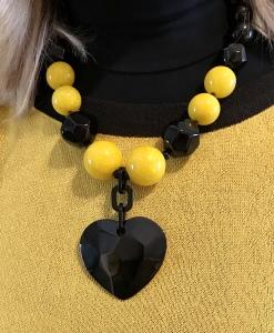 Dettaglio della collana indossata da Raffy, divertenti maxi boulle in plexiglas con grande cuore sfaccettato al centro.