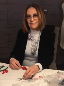 Cilla, al lavoro per la prossima collezione, indossa una sua creazione realizzata e cucita interamente a mano con passamanerie, perle naturali, madreperle, pietre dure ed elementi in plexiglas metallizzato.