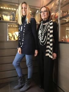Raffy indossa il ciondolo tre sfere nella nuance azzurro polvere e bianco e una collana lunga con perle bianche e boulle plexi. Cilla indossa tante collane in perla bianca abbinata al nero.