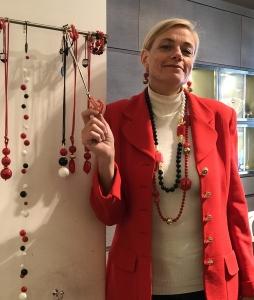 Sabrina indossa delle collane lunghe con boulle ed elementi in plexiglas nei toni del bianco rosso e blu, tutto illuminato da dettagli in oro lucido e satinato. Orecchini in parure
