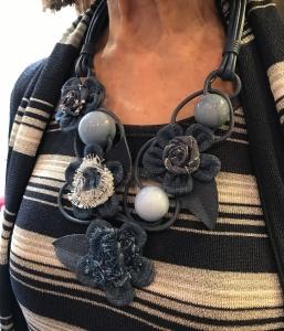 Dettaglio della meravigliosa collana indossata da Cilla. Una vera scultura interamente modellata e cucita a mano con fine lavorazione artigianale. Fiori e sfere si mixano per un effetto femminile e molto glamour.