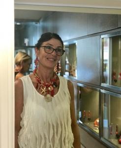 Sandra indossa una collana interamente realizzata a mano nei toni del corallo e oro, con tanti elementi a tema marino.