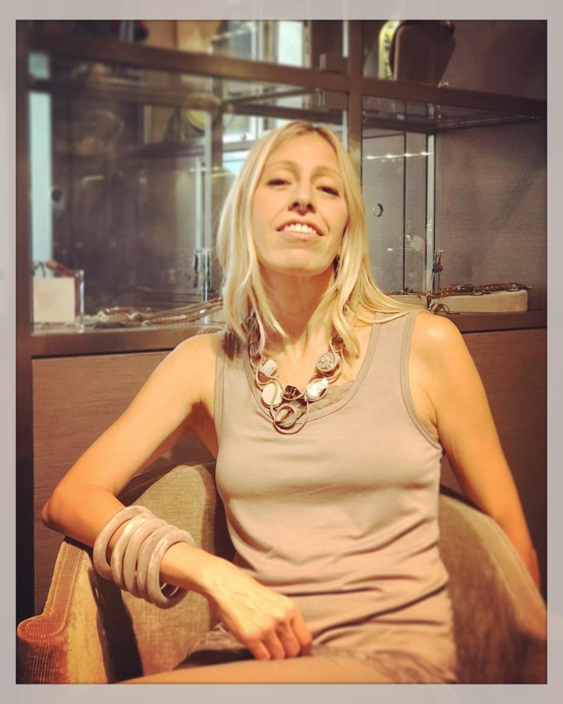 Raffy indossa una collana molto luminosa interamente realizzata e modellata a mano con filato in cotone cerato tortora chiaro. Preziosi elementi in pietra dura e perle sono come imprigionati tra le volute della collana. E' un pezzo unico di Cillabijoux Da abbinare tanti bangles in plexiglas nelle stesse nuance della collana.
