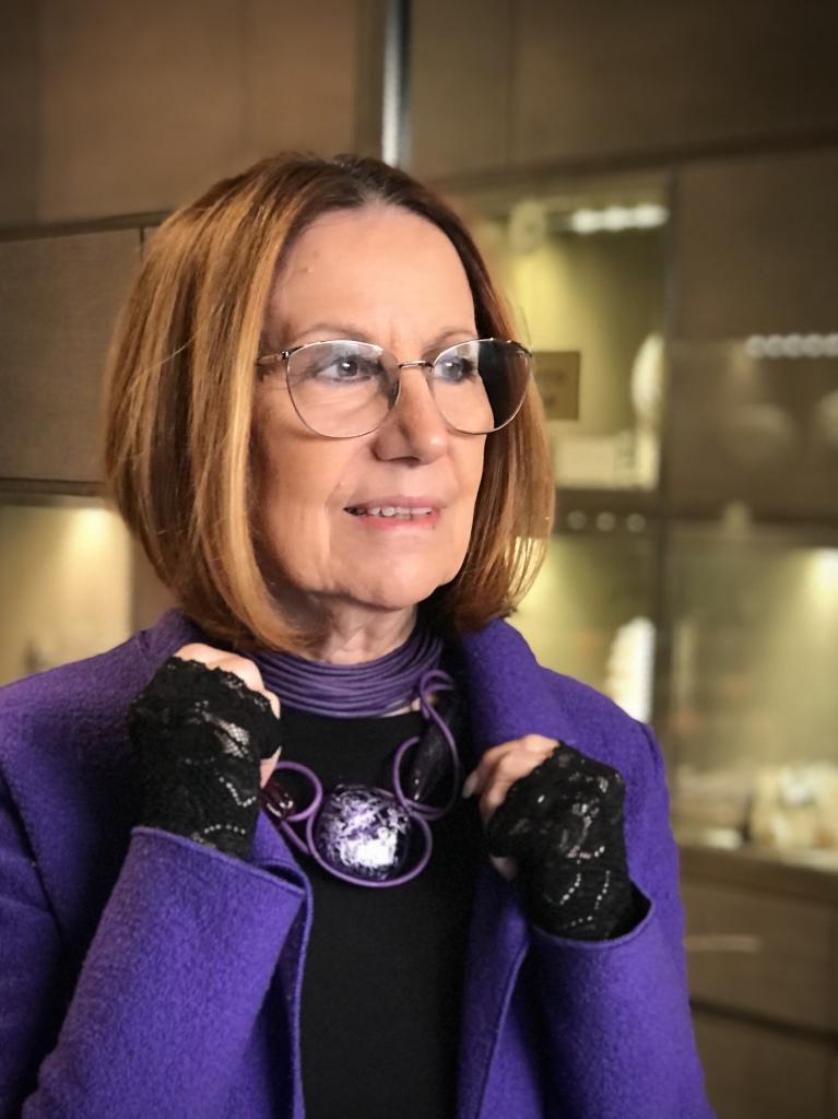 Cilla  indossa un collier de chain a fascia in filato di cotone cerato viola e una collana fantasia, interamente modellata a mano, con filato in cotone cerato e maxi elementi in plexiglas.