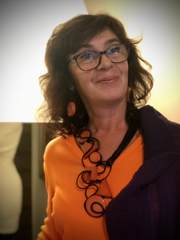 Sandra indossa una originalissima collana interamente realizzata e modellata a mano con filato in cotone cerato nero ed elementi geometrici in plexiglas laccati arancioni. Orecchini realizzati con gli stessi materiali.