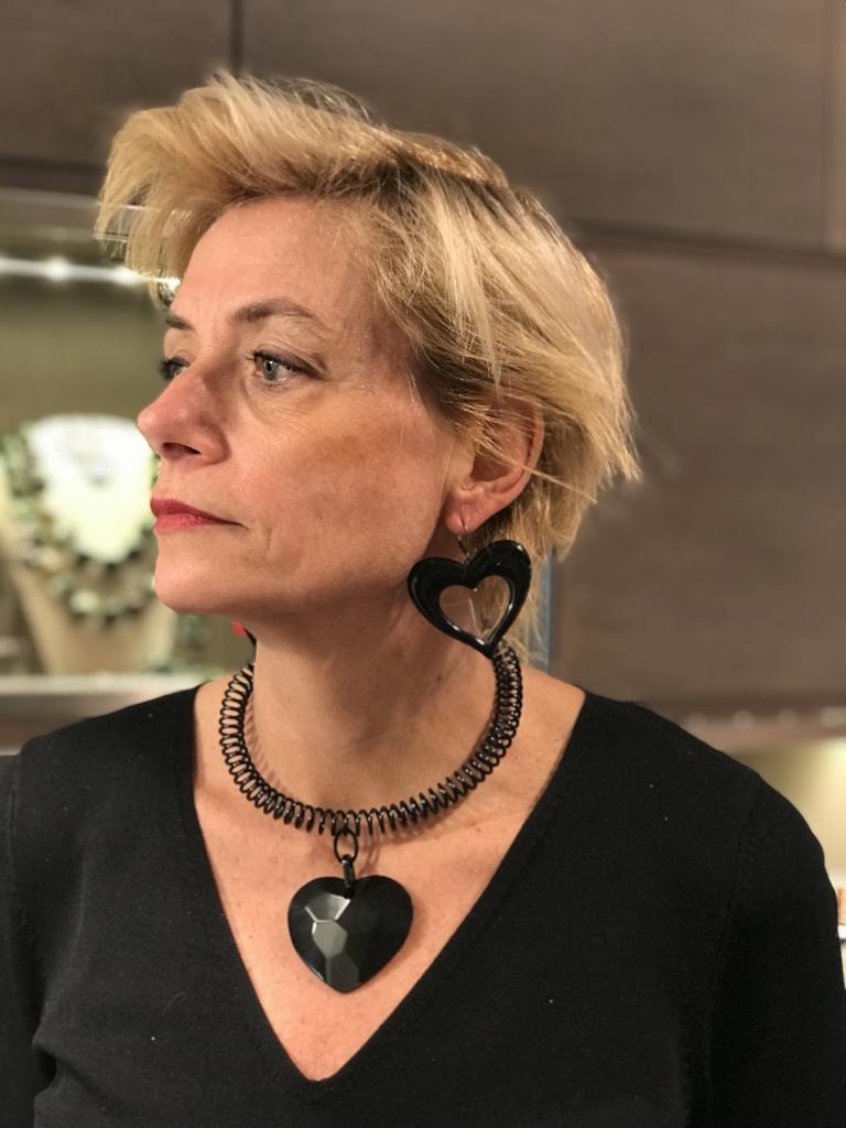 Sabrina indossa un originale girocollo dalla linea molto moderna, realizzato a mano con una molla laccata nera e grande ciondolo in plexiglas a forma di cuore, con lavorazione sfaccettata. Da abbinare maxi orecchini in plexiglas a forma di cuore.