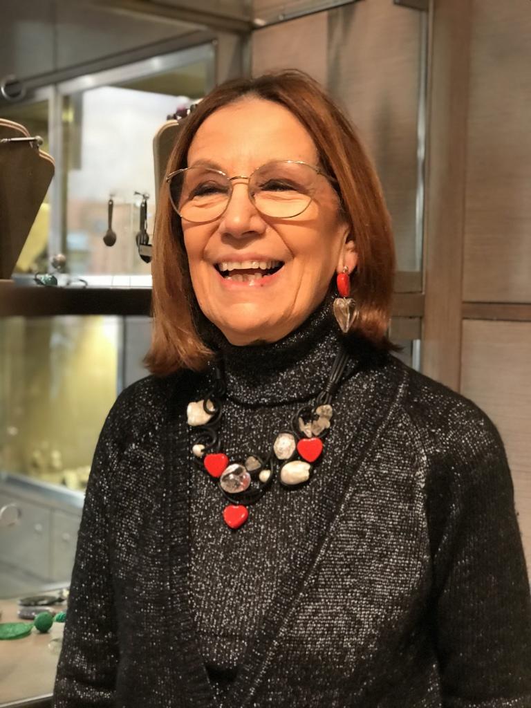 Cilla indossa una splendida collana interamente realizzata e modellata a mano con pietre dure, cristalli, perle e piccoli cuori rossi in plexiglas. E' un pezzo unico di Cillabijoux