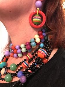 Dettaglio delle collane indossate da Sandra, un mare di colori che regalano vivacità e brio al tuo look. Particolare degli orecchini, realizzati con elementi in plexiglas multicolor.