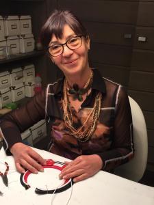 Anche Sandra è al lavoro sulla nuova collezione; lei indossa una collana a tanti fili in pietra dura con un grande fiore in corno vegetale.  Per uno stile più casual